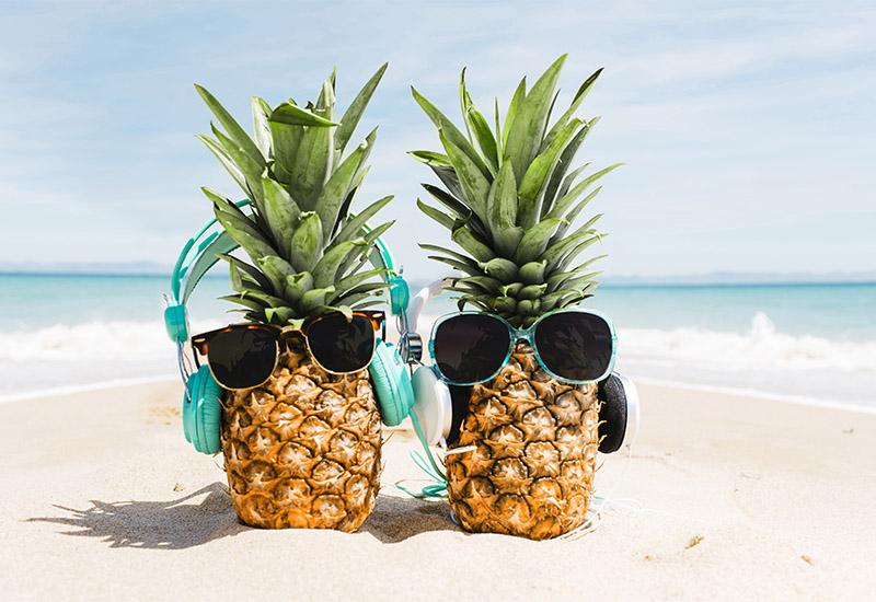 Zwei Ananas mit Sonnenbrillen stehen im weißen Sand an einem Strand. Im Hintergund sieht man türkises, welliges Meer. Beide haben als Accessoire neben den Sonnenbrillen auch noch Kopfhörer auf.