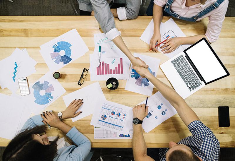 Das Bild zeigt eine Draufsicht auf einen Schreibtisch. Es ist von oben fotografiert, so als ob man über dem Tisch schwebt. An dem Tisch sitzen zwei Männer und zwei Frauen, die nur zum Teil zu sehen sind. Die Männer geben sich über den Tisch hinweg die Hand, so als ob sie ein Geschäft abgeschlossen hätten. Auf dem Tisch liegen viele Zettel mit Statistiken und Tabellen, ein Telefon und ein Laptop sowie zwei Handys.
