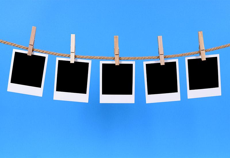 Mehrere Polaroid-Fotos sind nebeneinander an einer Leine aufgehängt.