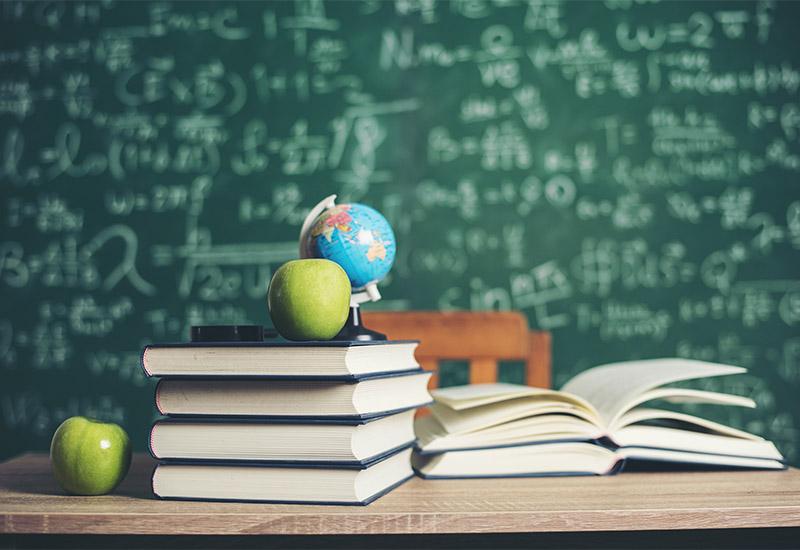 Im Hintergrund eine Schultafel, die in weißer Kreideschrift von oben bis unten mit mathematischen Formeln beschriftet ist. Vor der Tafel im Hintergrund steht ein Tisch mit einem etwas abgerückten Stuhl. Auf diesem Tisch, auf den wir von vorne Blicken liegen einige Bücher  auf zwei Stapeln. Auf dem höheren liegt ein Apfel neben einem kleinen Globus und einer Lupe? Auf dem anderen, kleineren Stapel liegt ein aufgeschlagenes Buch. Ein weiterer Apfel befindet sich links des größeren Stapels. Es hat den Anschein, als ob dort bis eben jemand gesessen und gelernt hätte.