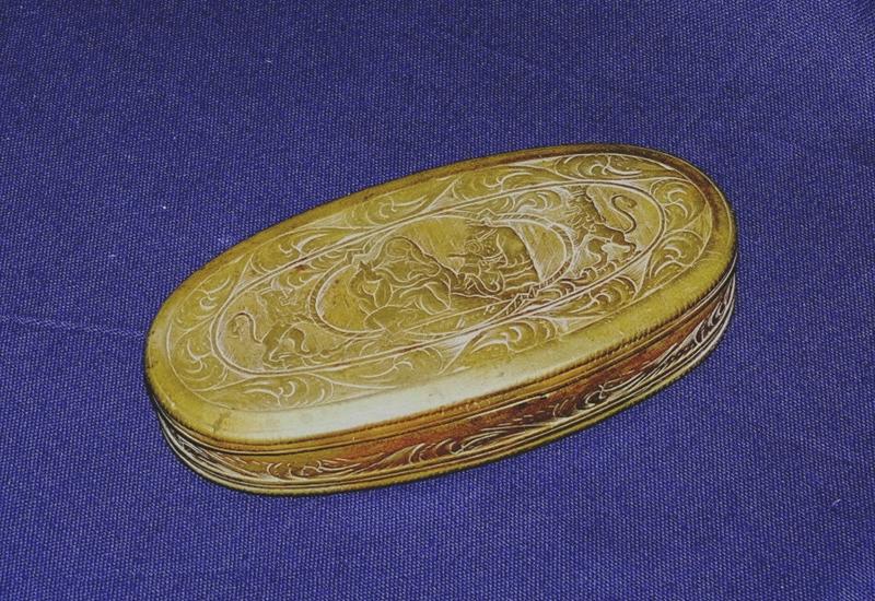 Diese ovale Tabakdose aus Messing ist eine holländische Arbeit und datiert in das 18. Jahrhundert. Der Deckel und Boden sind flächig mit gravierten Bildmotiven verziert, darunter wahrscheinlich eine Darstellung der Heiligen Familie im Tempel.