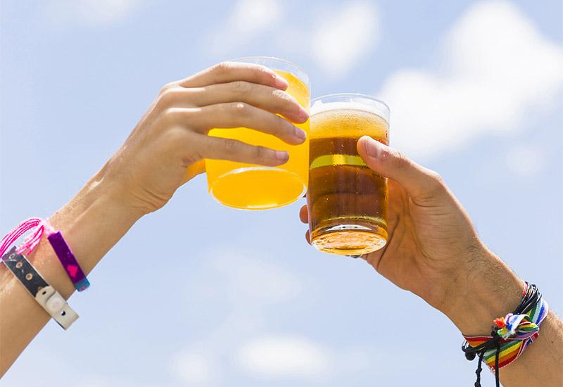 Zwei Hände stoßen vor dem blauen Himmel im Hintergrund, die Gläser, die sie halten zusammen. Beide tragen Festivalbändchen aber auch Freundschaftsbänder.