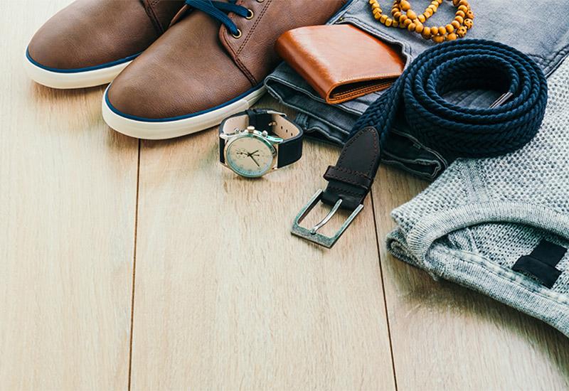 Auf dem Fußboden liegen Kleidung und Accessoires eines jungen Mannes. Ordentlich zusamengelegt sieht man einen Pullover, eine Jeans plus Gürtel, ein paar Schuhe, sowie ein Portemonnaie, eine Uhr und eine Kette oder ein Armband, vermutlich aus Holzperlen.