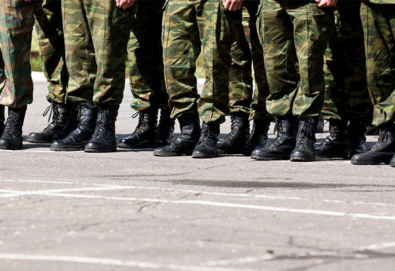Das Bild zeigt eine Reihe von uniformierten Beinen in Soldatenstiefeln, die nebeneinander auf einem Stein- bzw. Asphaltboden stehen. Allerdings nicht in Reih und Glied sondern eher locker.