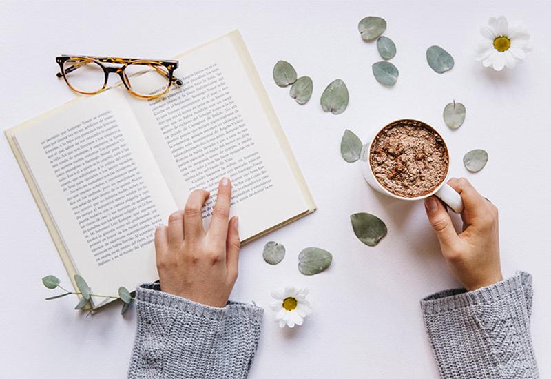 Von oben blickt man auf ein aufgeschlagenes Buch in dem eine menschliche Hand auf eine Zeile zeigt, so als ob sie mit dem Finger beim Lesen den Text entlang fährt. Die andere dazugehörige Hand hält eine Tasse mit einem bräunlichen Getränk. Vermutlich handelt es sich dabei um Kakao. Auf dem Buch liegt noch eine Brille. Einige Eukalyptusblätter und Margeritenblüten sind um das Buch und die Hände verstreut. Es sieht nach einem gemütlichen Lesenachmittag mit Lieblingskakao aus.
