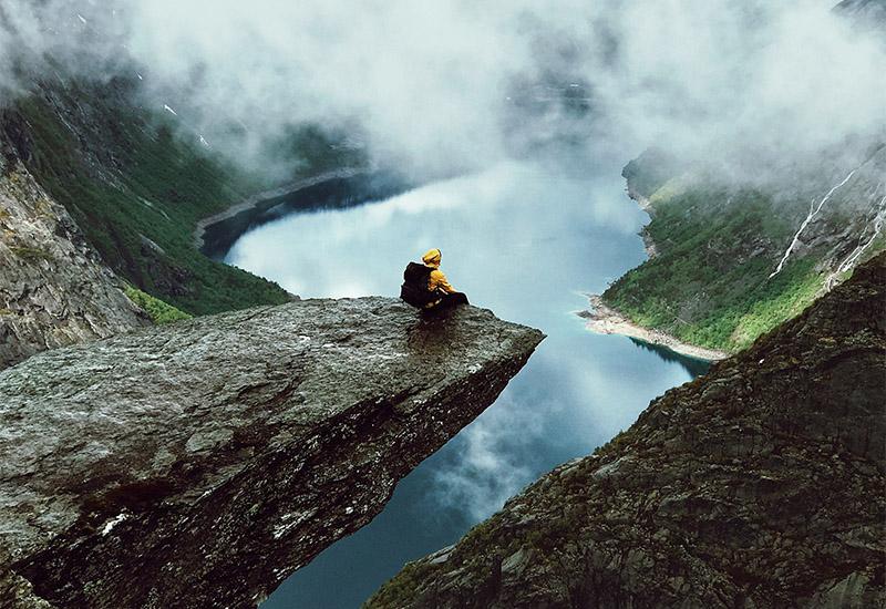 Am Rand einer ins Bild hinein ragenden Felsklippe sitzt eine Person und sieht in den vor ihr liegenden Abgrund und auf den See unter ihr, der sich zwischen Berghängen aufspannt. Die Gipfel der den See umgebenden Berge, von denen sich einige durch die Wolken abzeichnen sind schneebedeckt. Die Person in der gelben Jacke mit dem schwarzen Rucksack auf dem Rücken scheint allein zu sein in dieser Weite. Auch wie sie sich fühlt ist nicht erkennbar. Groß, da sie über allem thront, oder klein, angesichts dieser Naturhaften Gewalt, die so ohne jegliches Zutun des Menschen einfach so da ist?