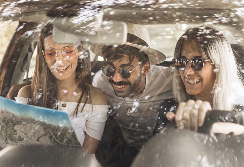 Wir blicken durch die Windschutzscheibe in das Innere eines Autos, in dem drei junge Leute sitzen. Sie tragen Sonnenbrillen und lächeln oder lachen alle. Die Beifahrerin auf der rechten Seite guckt in eine Karte. Der junge Mann mit Hut, der auf der Rückbank sitzt, beugt sich zu ihr nach vorne und sieht über ihre Schulter ebenfalls in die Karte. Ebenso, wie die junge Frau mit Nasenpiercing, die am Steuer sitzt.