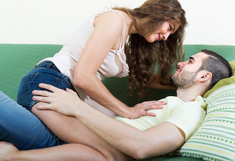 Eine junge Frau sitzt auf einem jungen Mann, der auf einem Sofa liegt. Vielleicht haben sie gleich Sex. Eigentlich sehen sie dafür zu unerotisiert aus.
