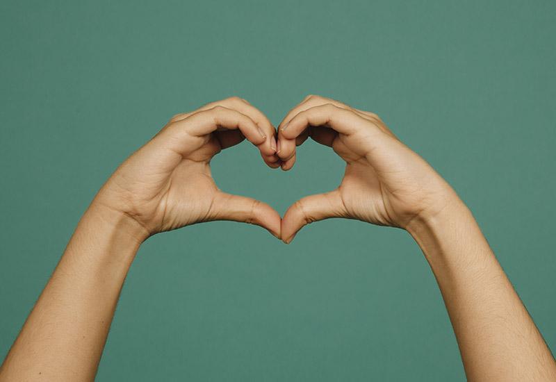 """Das Bild zeigt zwei Hände vor einem türkis-grünen Hintergrund, die ein Herz formen. Wir kennen diese Geste alle. Meistens bedeutet sie wohl etwas wie """"Ich liebe Dich"""" oder """"ich liebe Euch"""". Auch Fußballspiele bei der WM haben das Hand-Herz oft in die Kameras gehalten."""