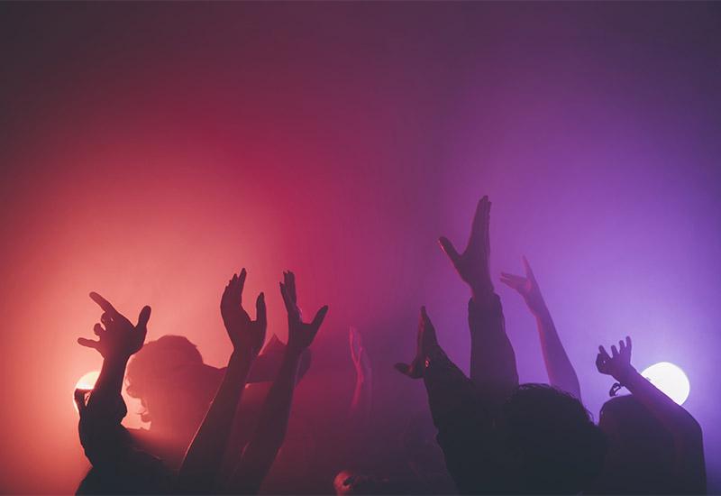 In rosa-lila-farbigem Licht recken sich zahlreiche Arme von Tanzenden in die Höhe. Im Hintergrund sieht man zwei helle Scheinwerfer. Man kann sich beim Betrachten des Bildes gut vorstellen, dass die Musik dort ziemlich laut ist und die Leute viel Spass beim Tanzen haben.