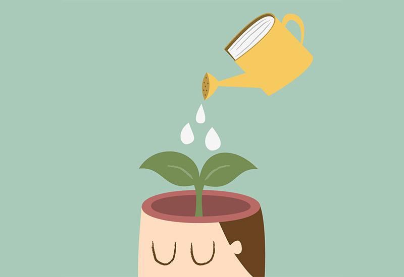Aus einer Gießkanne, die wie ein Buch aussieht, wird eine Pflanze begossen. Die Pflanze steht aber nicht in einem normalen Blumentopf, sondern wächst aus einem nach oben offenen Kopf heraus.