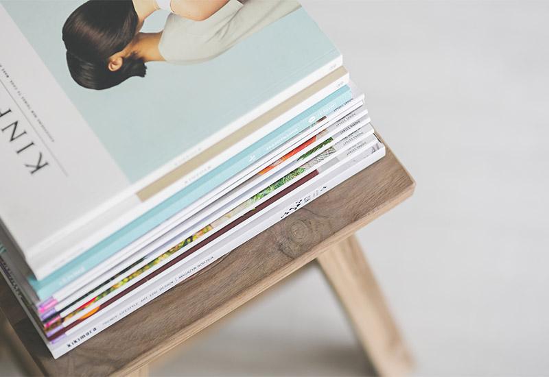 Man sieht einen Stapel Magazine und Zeitschriften ordentlich übereinander gestapelt auf einem Hocker oder Stuhl liegen.